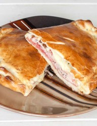 Home-made calzone loaded with various Italian cold cuts