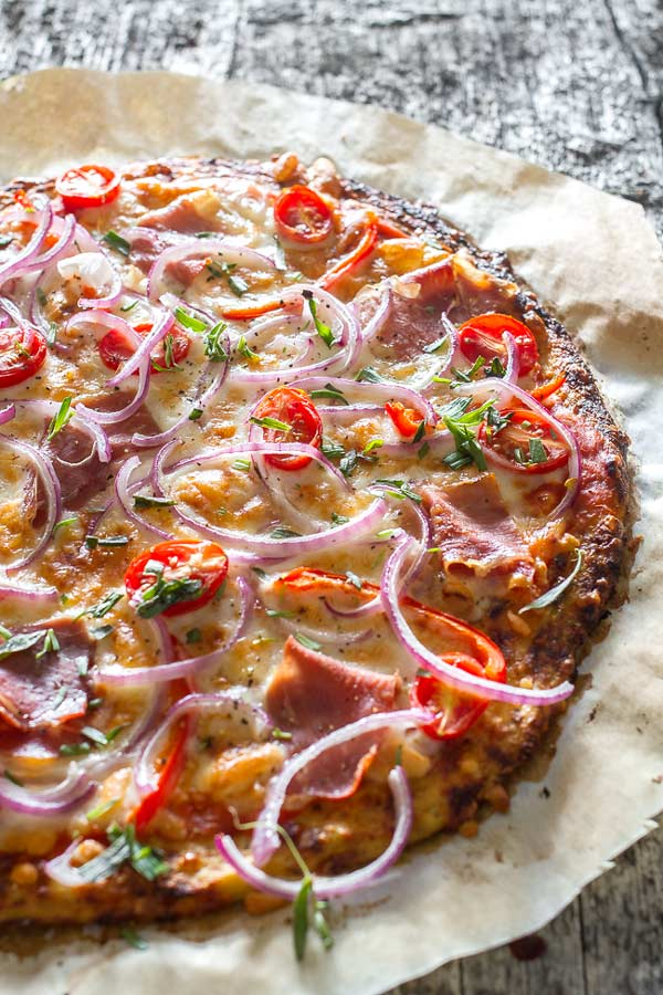 Delicious healthy pizza recipe featuring mozzarella cheese and prosciutto, on a delicious thin crust made from cauliflower sprinkled with fresh tarragon.